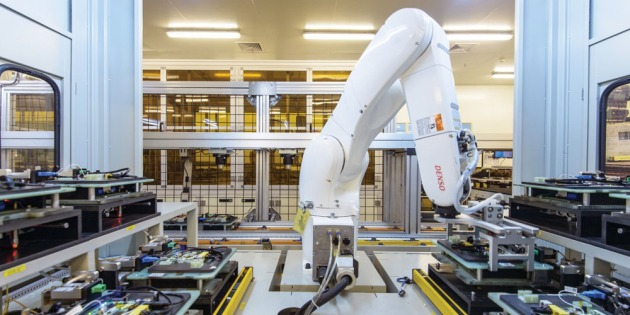 A robot arm moves circuit boards around for testing inside CIG's factory in Shanghai. Previously the work was done by hand. Credit MIT